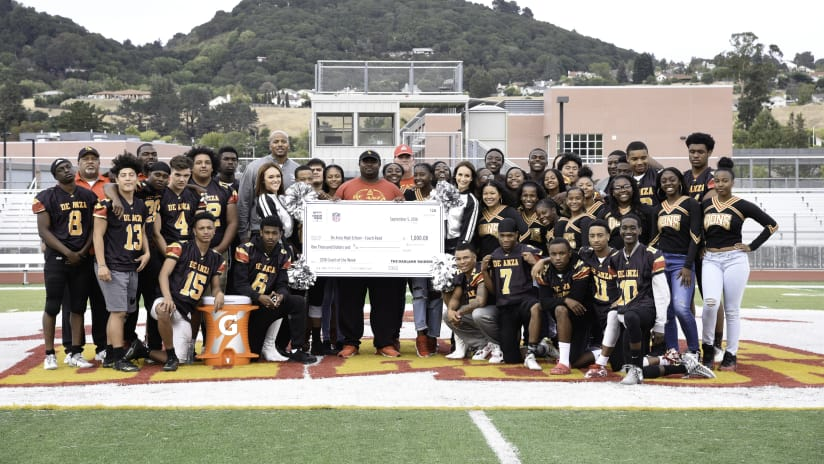 De Anza High School's football coach, Tyree Reed is awarded with the Tom Flores High School Coach of the Week by Raiders alumnus, Courtney Anderson, and the Raiderettes at De Anza High School, Wednesday, September 12, 2018, in Richmond, California.