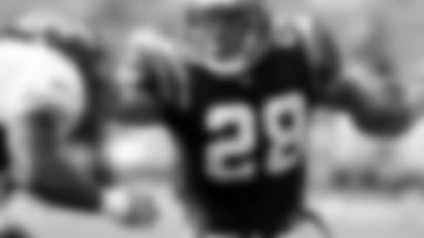 Bengals running back Corey Dillon pushes away Denver Broncos defender Al Wilson.