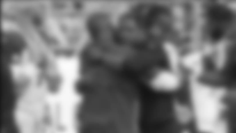 El entrenador de Cardenales Steve Wilks (derecha) abraza al coordinador defensivo Al Holcomb después de que Wilks consiguió el domingo su primera victoria como entrenador en la NFL, luego que su equipo venció 28-18 a 49ers.