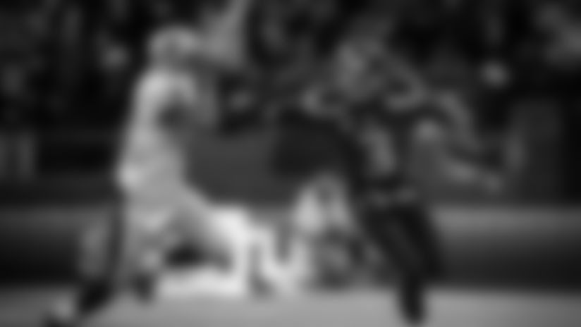 Seahawks quarterback Russell Wilson offers a stiff-arm to Saints safety Roman Harper.