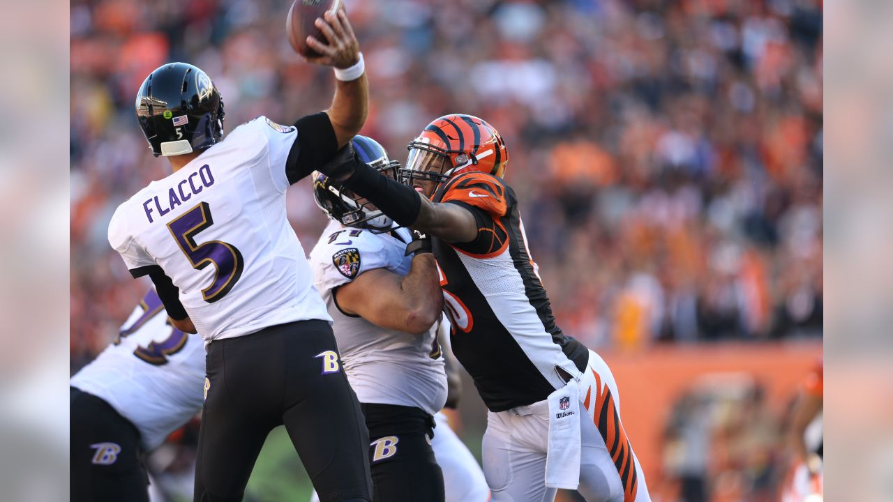 Carlos Dunlap hits Joe Flacco as he throws during a 2014 contest against Baltimore.