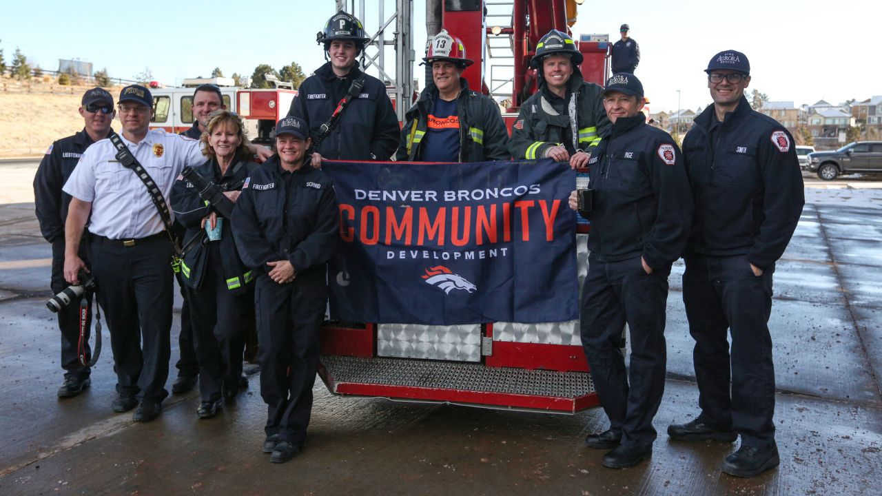 Head Coach Vic Fangio poses for a photo with local members of Aurora Fire Rescue during a visit for Random Acts of Kindness Week on February 20, 2019.