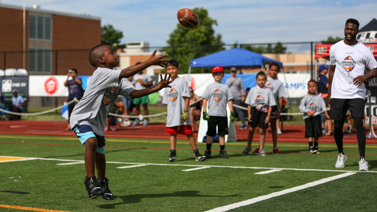 Emmanuel Sanders interacts with children at his youth football camp at Thomas Jefferson High School in Denver on July 1, 2019.