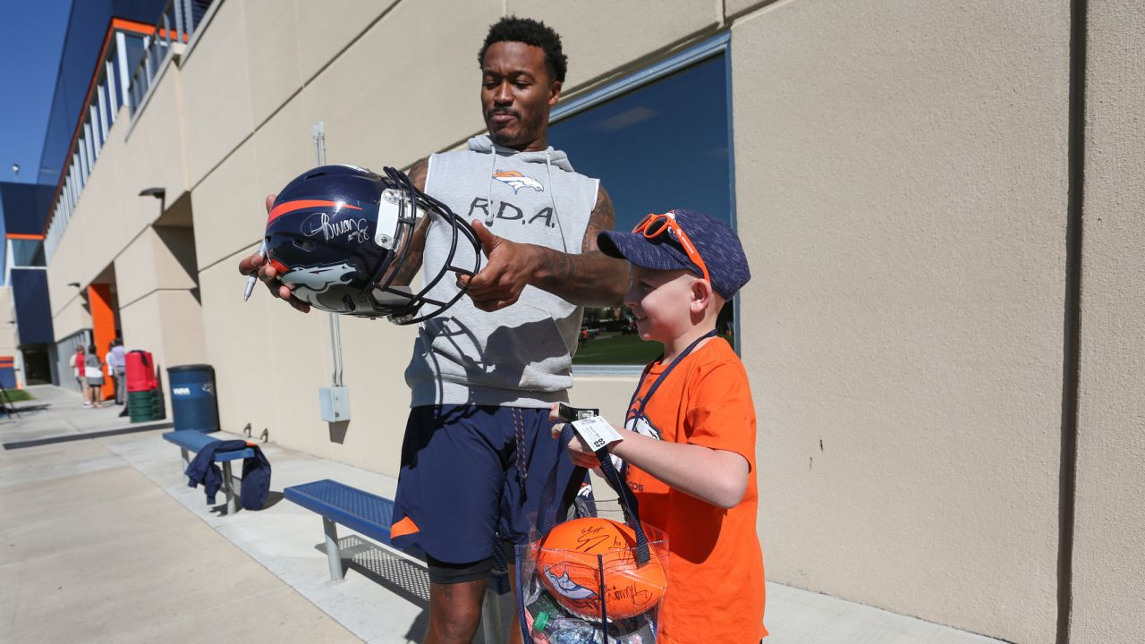 Chase, a Children's Hospital Colorado Junior Reporter, receives an autographed helmet from Demaryius Thomas at UCHealth Training Center on September 26, 2018.