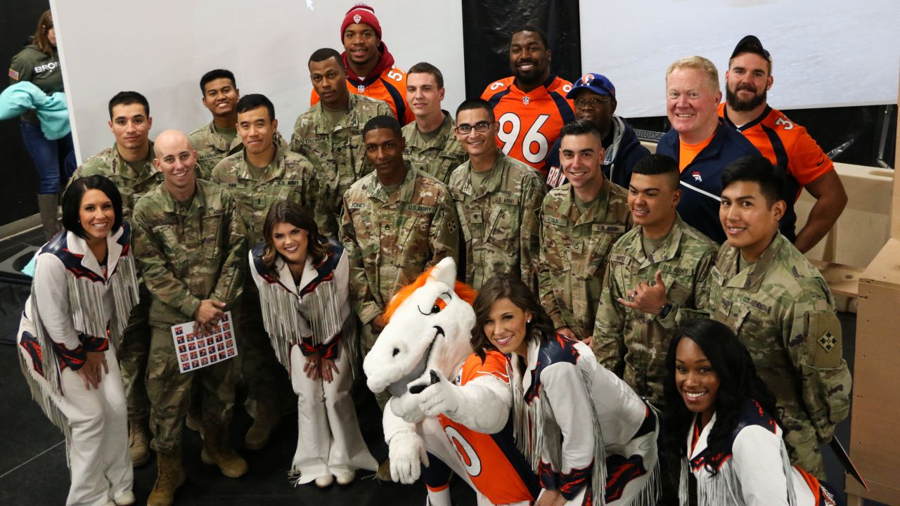 Players, cheerleaders, staffers and military members pose during the Denver Broncos' Salute To Service Caravan at Fort Carson, Colorado on October 30, 2018.