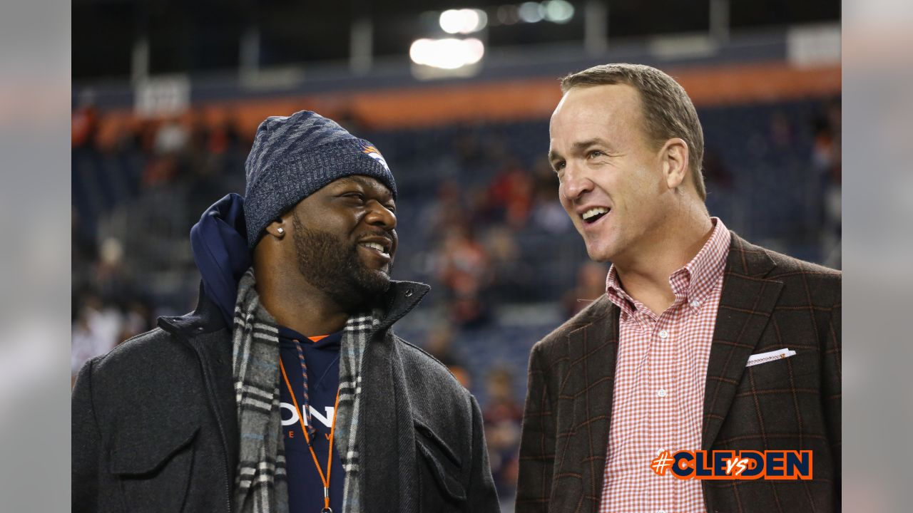 Al Wilson talks with Peyton Manning before the Broncos' Week 15 game against the Cleveland Browns at Broncos Stadium at Mile High on December 15, 2018.