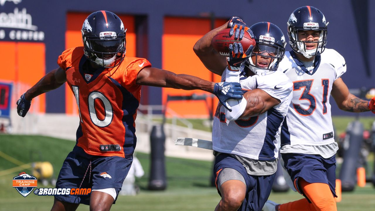 Cornerback Chris Harris Jr. (25) returns an interception as wide receiver Emmanuel Sanders (10) gets a hand on him during the 11th day of training camp on August 9, 2018, at UCHealth Training Center.