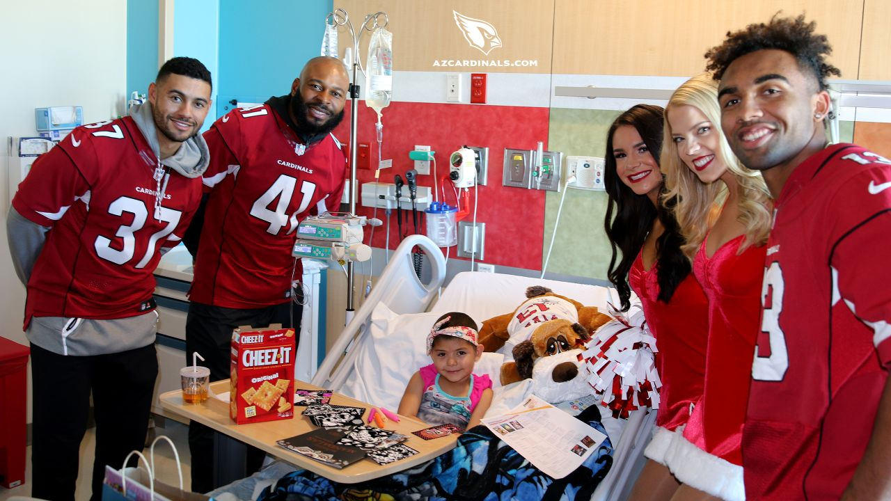 RB D.J. Foster (37), S Antoine Bethea (41) and WR Christian Kirk (13) pose with a patient and the Cardinals cheerleaders