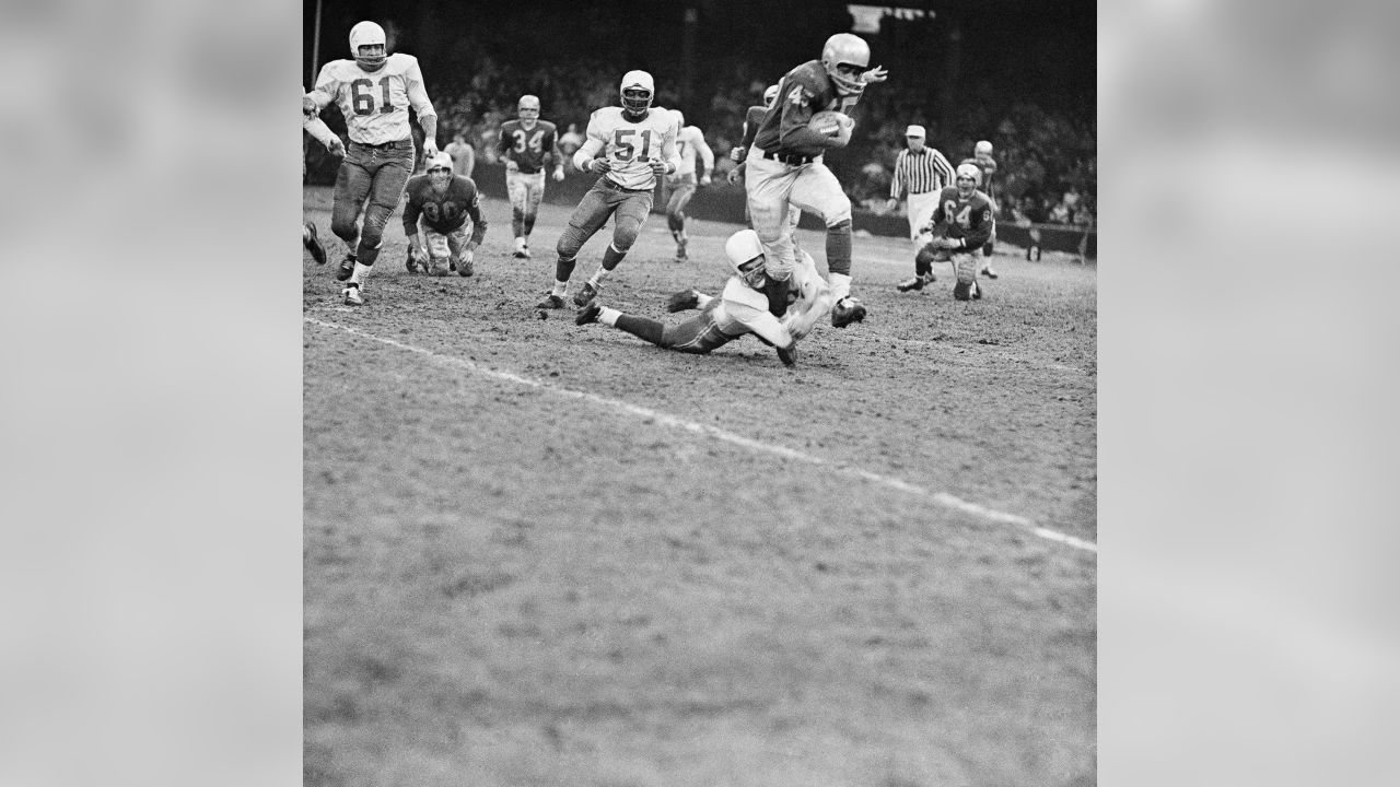 Detroit Lions halfback Dan Lewis (45) looks like he is about to be toppled by Chicago Cardinals back Jim Wagstaff (on ground), but Lewis was too fleet for him. He ran a good ten yards more in this fourth quarter play before another player nailed him. At rear is Cardinals linebacker Ted Bates (51). The Lions scored early and kept a healthy lead throughout the game to win 54-21, on Dec. 7, 1959 in Detroit.