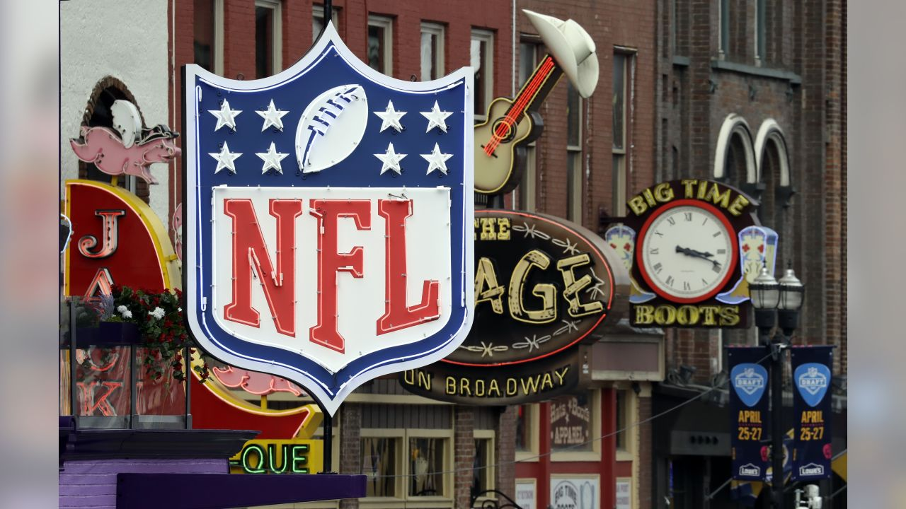 A temporary NFL neon sign joins the permanent ones along Broadway as preparation continues for the NFL Draft Tuesday, April 23, 2019, in Nashville, Tenn. The NFL Draft is scheduled to be held Thursday through Saturday. (AP Photo/Mark Humphrey)