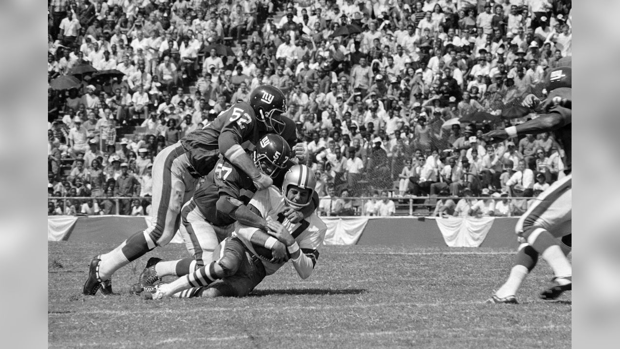 Dallas Cowboy quarterback Don Meredith (17) is tackled after an 8-yard run in the second quarter of Sunday's game at the Cotton Bowl against the New York Giants September 24, 1967. Making the tackle are Giant Linebackers Bill Swain (52) and Vince Costello (57). Meredith led the cowboys to a 38-24 victory over the Giants. (AP Photo)