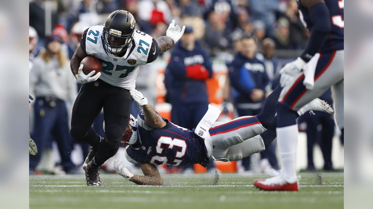 Jacksonville Jaguars running back Leonard Fournette (27) carries the ball in front of New England Patriots strong safety Patrick Chung (23) during an NFL AFC Championship football game on Sunday, Jan. 21, 2018 in Foxborough, Mass. (Aaron M. Sprecher via AP)
