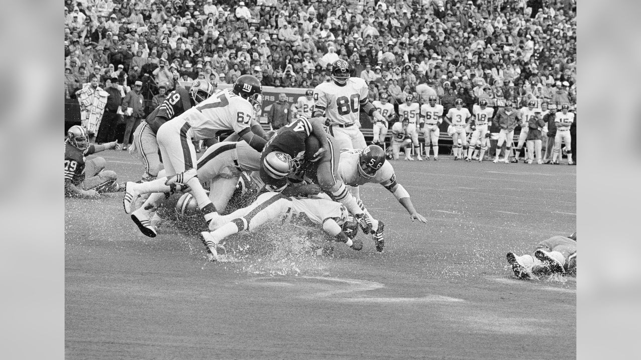 San Francisco 49ers Ken Willard (40) is shown in a tangle of New York Giants on a wet field in San Francisco, 1973. Other players unidentified.  (AP Photo)