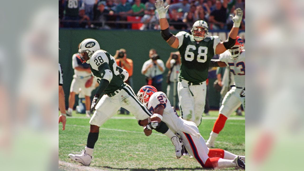 New York Jets running back Curtis Martin (28) crosses the goal line for a five yard touchdown run as Buffalo Bills defender Ken Irvin (27) fails to tackle him during the second quarter Sunday, Sept. 17, 2000, in East Rutherford, N.J. The Jets are 3-0 for the first time since 1966 after defeating the Bills 27-14. Jets' Kevin Mawae (68) signals touchdown in background. (AP Photo/Bill Kostroun)
