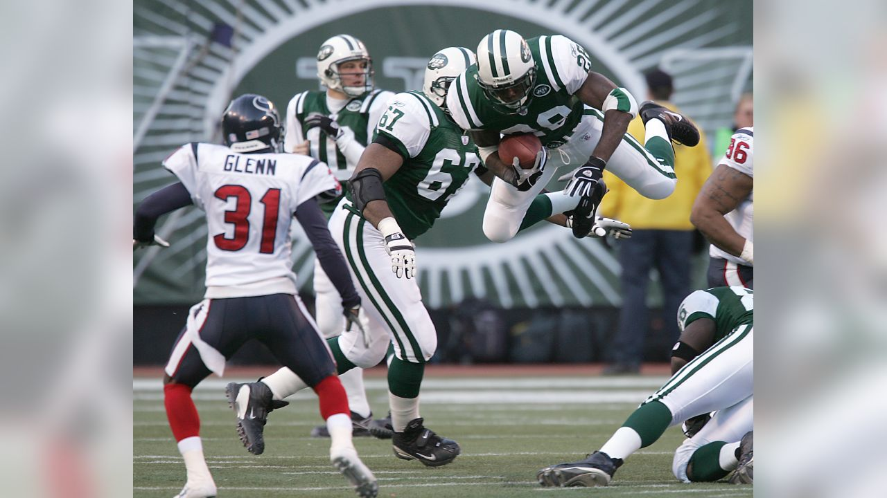 New York Jets' running back Curtis Martin (28) leaps over the Houston Texans' defense in the second quarter of play on Sunday, Dec. 5, 2004, at Giants Stadium in East Rutherford. Texans' Aaron Glenn (31), Jets' Chad Pennington (10), and Kareem McKenzie (67) looks on. (AP Photo/Michael Kim)