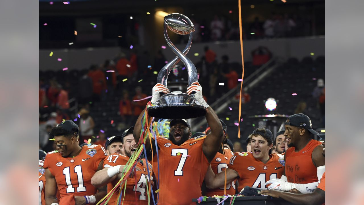 Clemson defensive end Austin Bryant (7) holds up the trophy as the team celebrates their 30-3 win against Notre Dame in the NCAA Cotton Bowl semi-final playoff football game, Saturday, Dec. 29, 2018, in Arlington, Texas. Clemson won 30-3. (AP Photo/Jeffrey McWhorter)