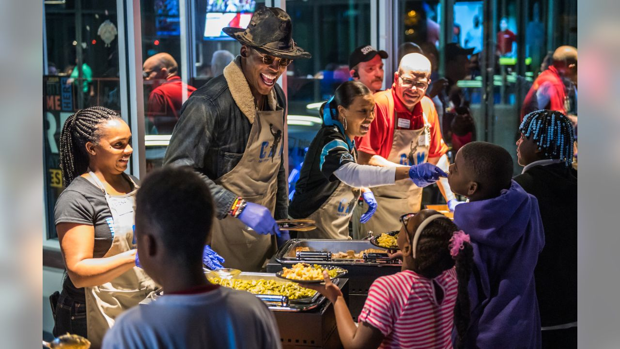 Cam Newton helps serve Thanksgiving dinners to children during his annual Cam's Thanksgiving Jam at Topgolf Charlotte on Monday, November 19, 2018.