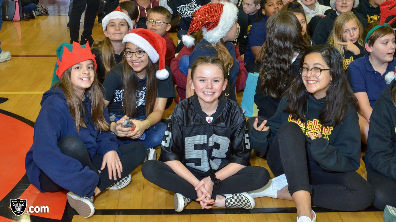 """The Raiders, represented by alumnus Reggie Kinlaw and the Raiderettes, and the Dairy Council of Nevada partner to promote healthy eating and a physically active lifestyle among students in the Clark County School District by awarding the school district with a $20,000 """"Hometown"""" grant and hosting a Fuel Up to Play 60 football clinic at Ralph Cadwallader Middle School, Thursday, December 13, 2018, in Las Vegas, Nevada."""