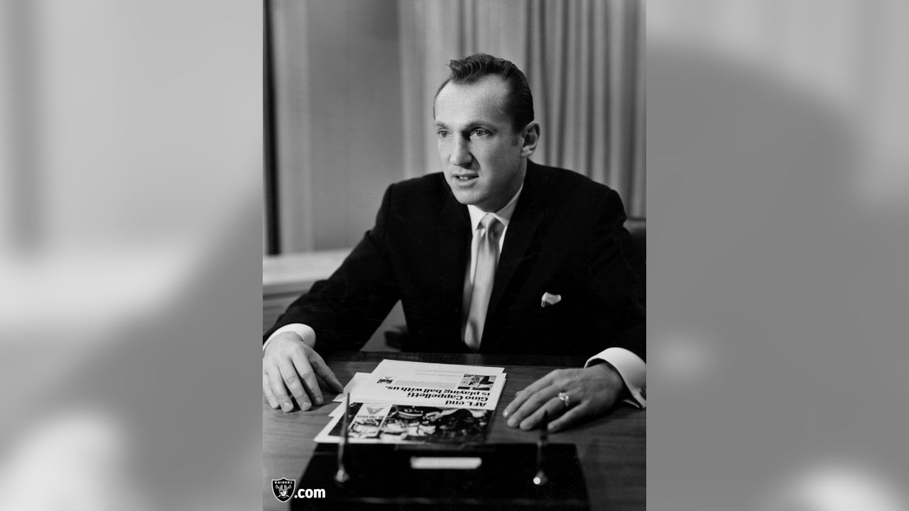 This is a photo of AFL Commissioner, Al Davis seated at his desk with an article about AFL end Gino Cappelletti.