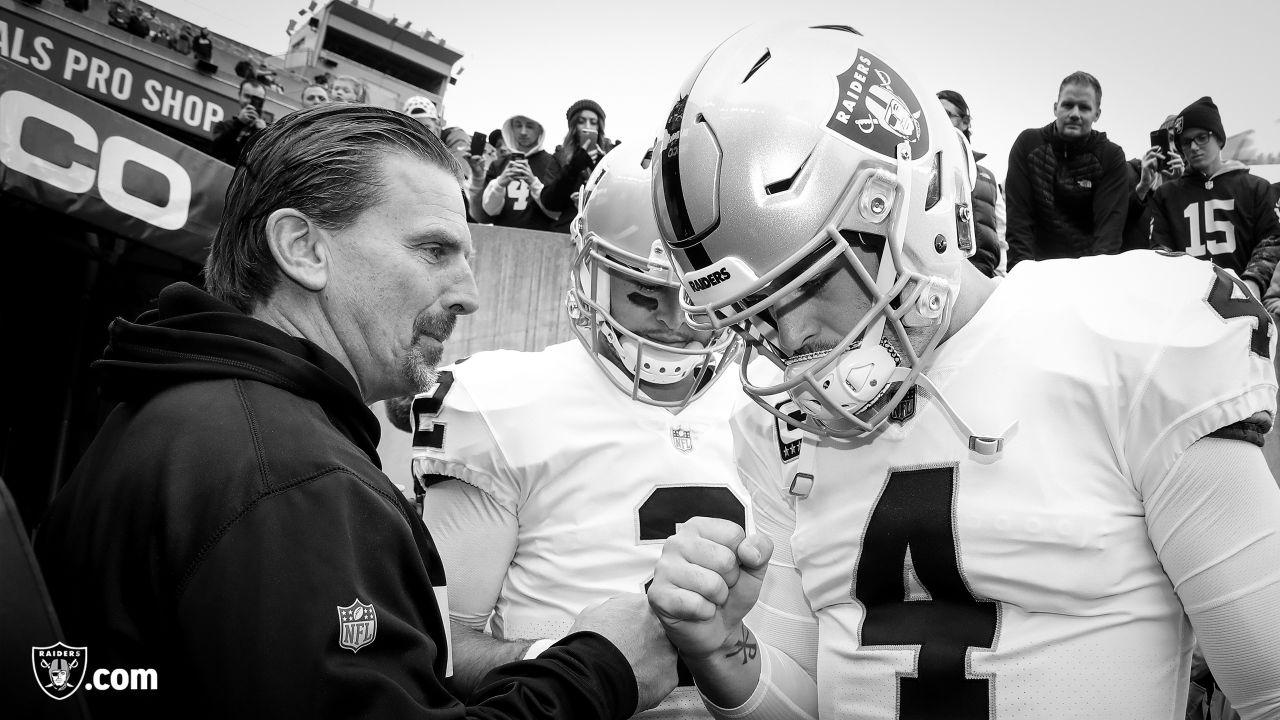 Oakland Raiders offensive coordinator Greg Olson, quarterback AJ McCarron (2), and quarterback Derek Carr (4) huddle up before their regular season game against the Cincinnati Bengals at Paul Brown Stadium, Sunday, December 16, 2018, in Cincinnati, Ohio. The Oakland Raiders lost 30-16.