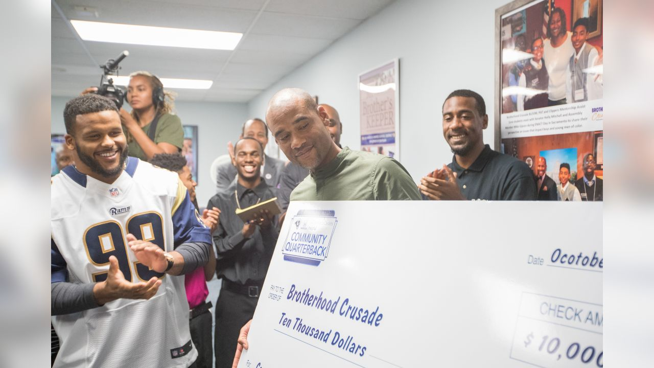 Defensive tackle (99) Aaron Donald of the Los Angeles Rams hands a check for $10,000 to the Brotherhood Crusade, Tuesday, October 22, 2018, in Los Angeles, CA. (Jeff Lewis)
