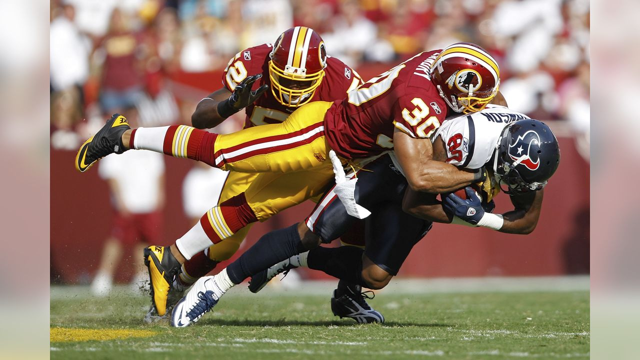 Houston Texans wide receiver Andre Johnson is stopped by Washington Redskins safety LaRon Landry (30) and linebacker Rocky McIntosh during the first half of an NFL football game in Landover, Md., on Sunday, Sept.. 19, 2010.  (AP Photo/Evan Vucci)