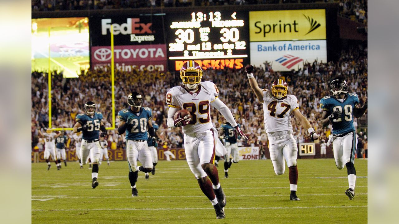 Washington Redskins wide receiver Santana Moss (89) races to the end zone on a 68-yard reception for a touchdown to win the game 36-30 against the Jacksonville Jaguars during overtime of a NFL football game, Sunday, Oct. 1, 2006, in Landover, Md. Redskins tight end Chris Cooely (47) celebrates as Jaguars linebacker Nick Greisen (55), safety Donovin Darius (20) and cornerback Brian Williams (29) pursue.(AP Photo/Nick Wass)