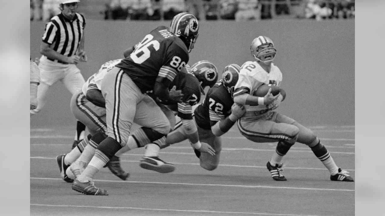 Dallas Cowboys' quarterback Roger Staubach grimaces as he loses yards during second quarter action Nov. 28, 1974 in Irving, Texas. Making the tackle is Washington Redskins Verlon Biggs (86), Ron McDole (79) and Diron Talbert (72). (AP Photo/Ferd Kaufman)