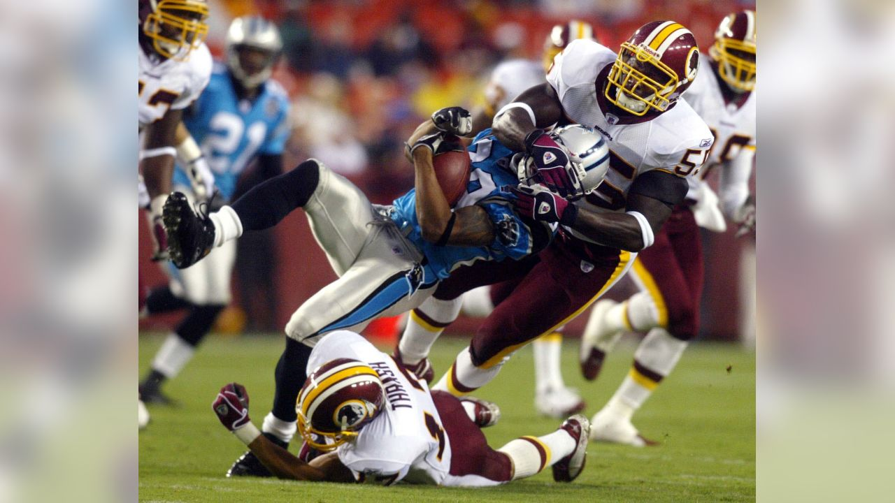 Washington Redskins special teams players James Thrash, bottom, and Kevin Mitchell, right, tackle Carolina Panthers kick returner Steve Smith on Saturday, Aug. 14, 2004 at FedEx field in Landover, Md.  (AP Photo/Evan Vucci)