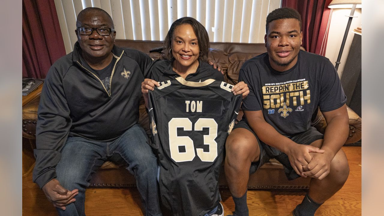 Dr. Michael Tom, left, Vanessa Tom, center, and Zach Tom, right, hold a Cameron Tom fan jersey at their home in Baton Rouge. Zach is Cameron's younger brother and is an offensive lineman at Wake Forest University. New Orleans Saints OL Cameron Tom grew up in Baton Rouge, La.