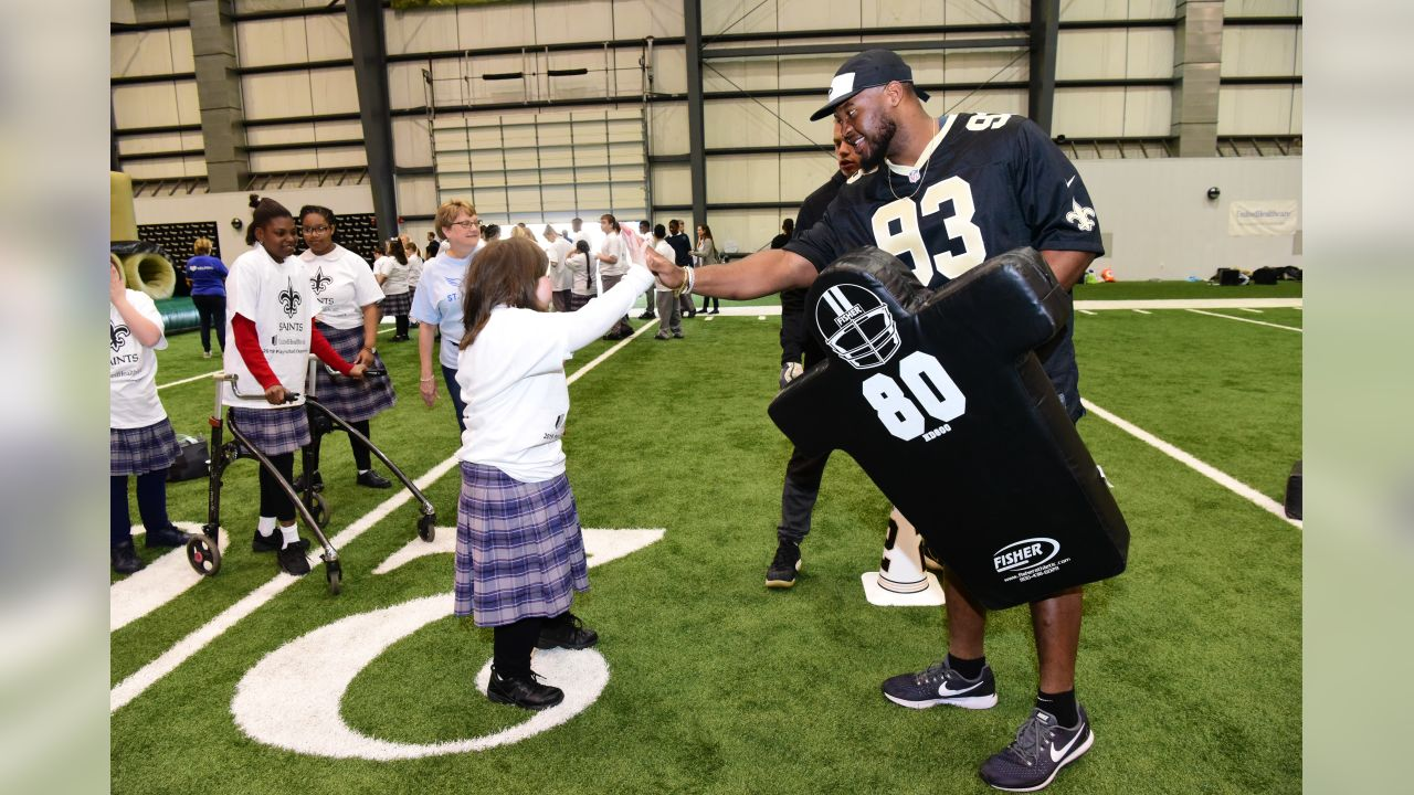 Students from St. Michael's Special School enjoy a football workout with Saints players at the Saints facility with United Health Care volunteers.