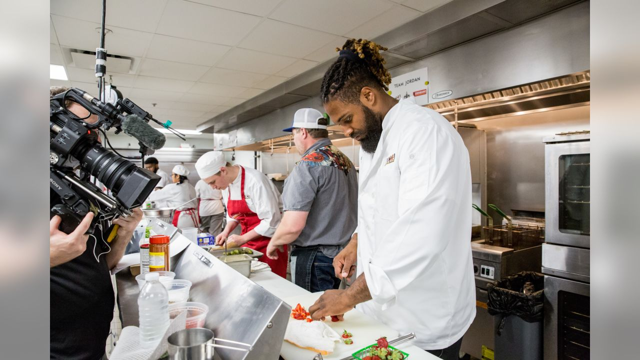 Cameron Jordan assists Chef Stephen Stryjewski in food prep at the New Orleans Center for Creative Arts (NOCCA). Saints players Cameron Jordan and Taylor Stallworth, and Saints legends Michael Lewis and Jeff Charleston teamed up with prominent New Orleans chefs and NOCCA students for a cooking competition.