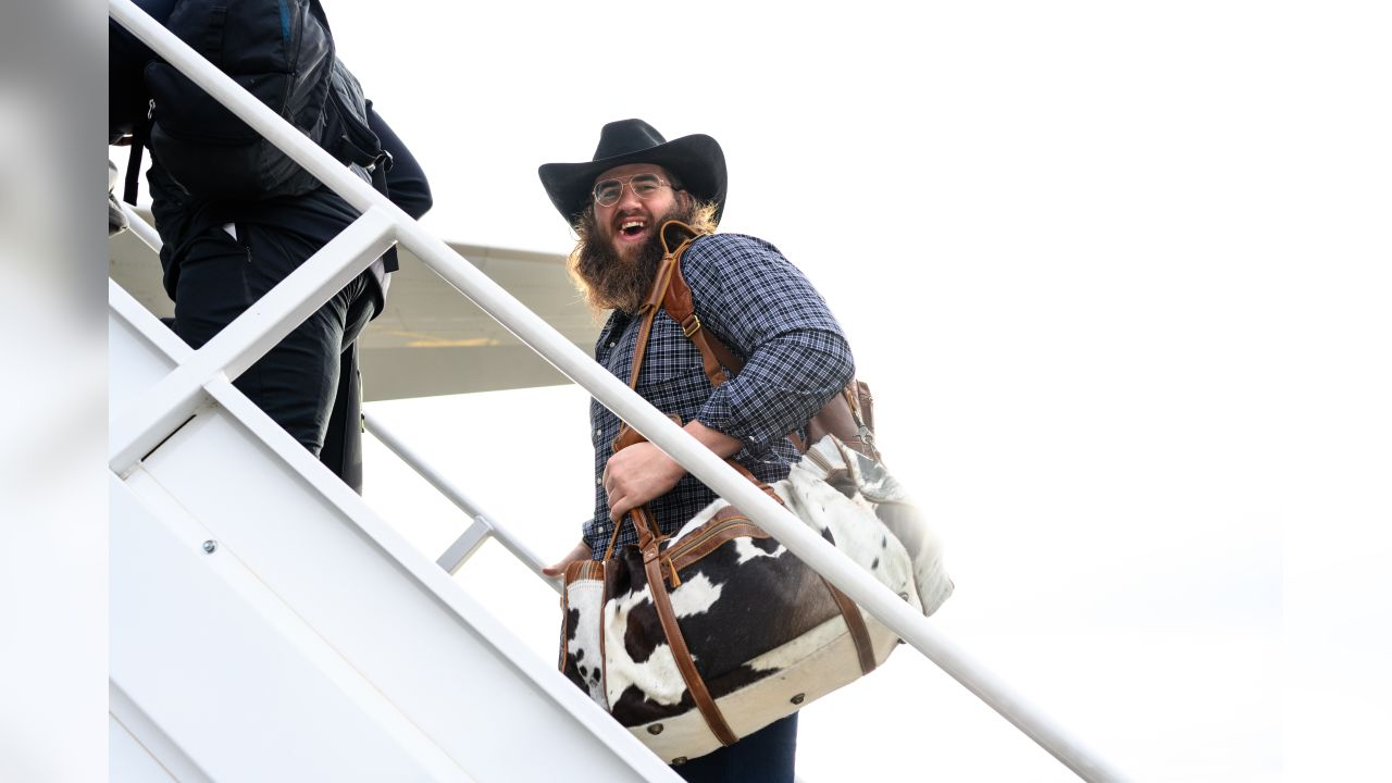 Seahawks offensive lineman Jordan Roos boards the team's charter with his signature cowboy hat with an accompanying Western-themed bag.