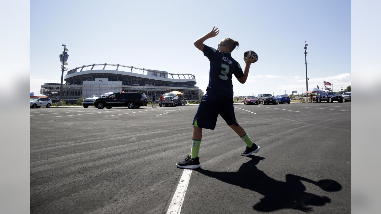 Trace Anderson, of Thornton, Colo., wears a Seattle Seahawks quarterback Russell Wilson replica jersey as he throws the ball with a friend in the parking lot of Mile High Stadium before the Seahawks face the Denver Broncos in an NFL football game Sunday, Sept. 9, 2018, in Denver. (AP Photo/Jack Dempsey)