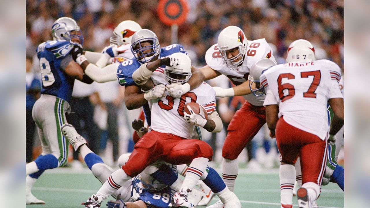 Running back Ron Moore (30) of the Phoenix Cardinals is held to a one yard gain as he is tackled by Cortez Kennedy (96) of the Seattle Seahawks during the third quarter of their NFL game in Seattle, Washington, Dec. 19, 1993. Watching the play is Joe Wolf (68) of the Cardinals. Phoenix beat Seattle in overtime, 30-27. (AP Photo/Bill Chan)