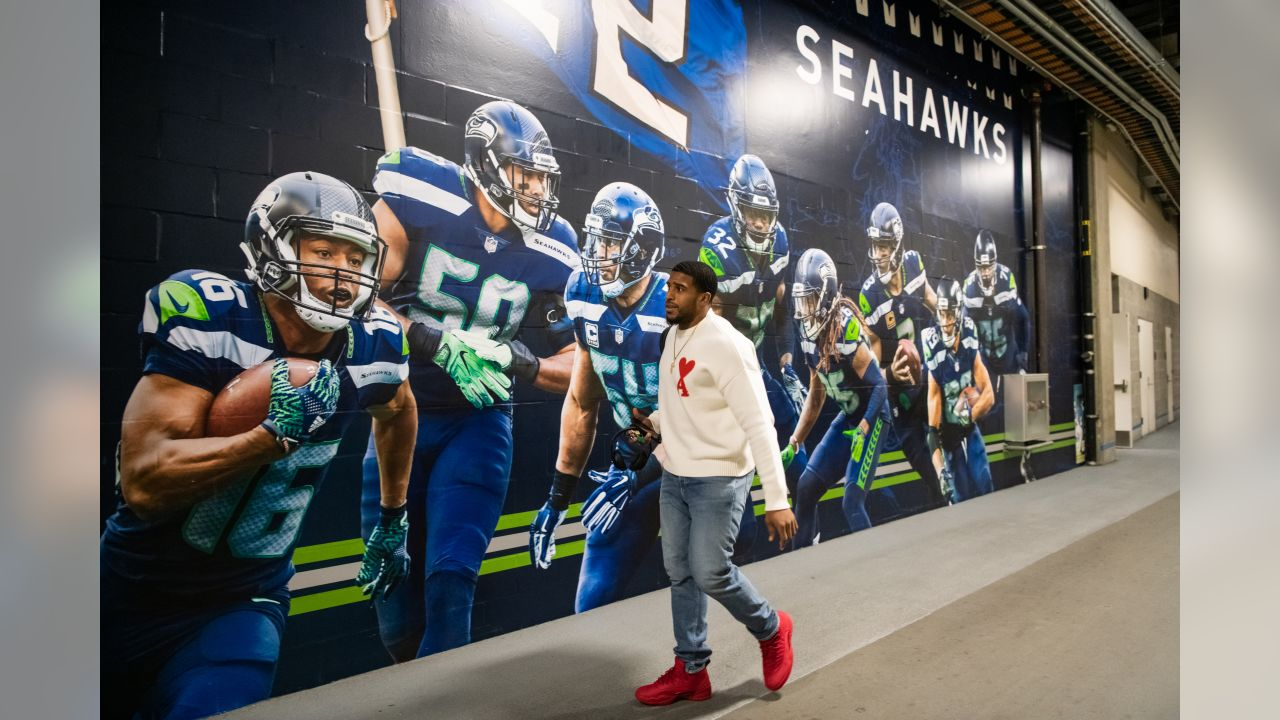 Linebacker Bobby Wagner walks to the Seahawks locker room via a back hallway featuring a wall mural of players including himself.