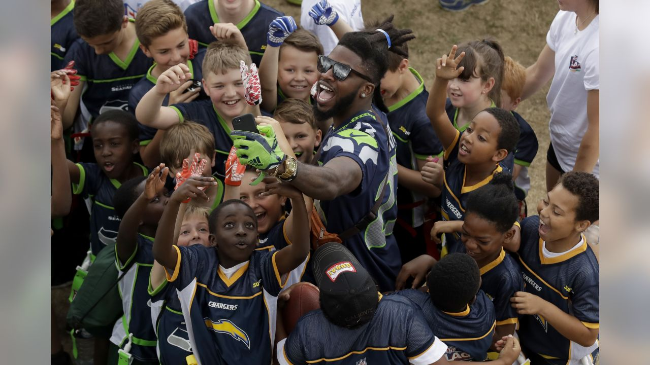 Seattle Seahawks' cornerback Neiko Thorpe takes a selfie with children during an NFL flag schools event at King's House Sports Ground in Chiswick, west London, Wednesday, July 18, 2018. (AP Photo/Matt Dunham)