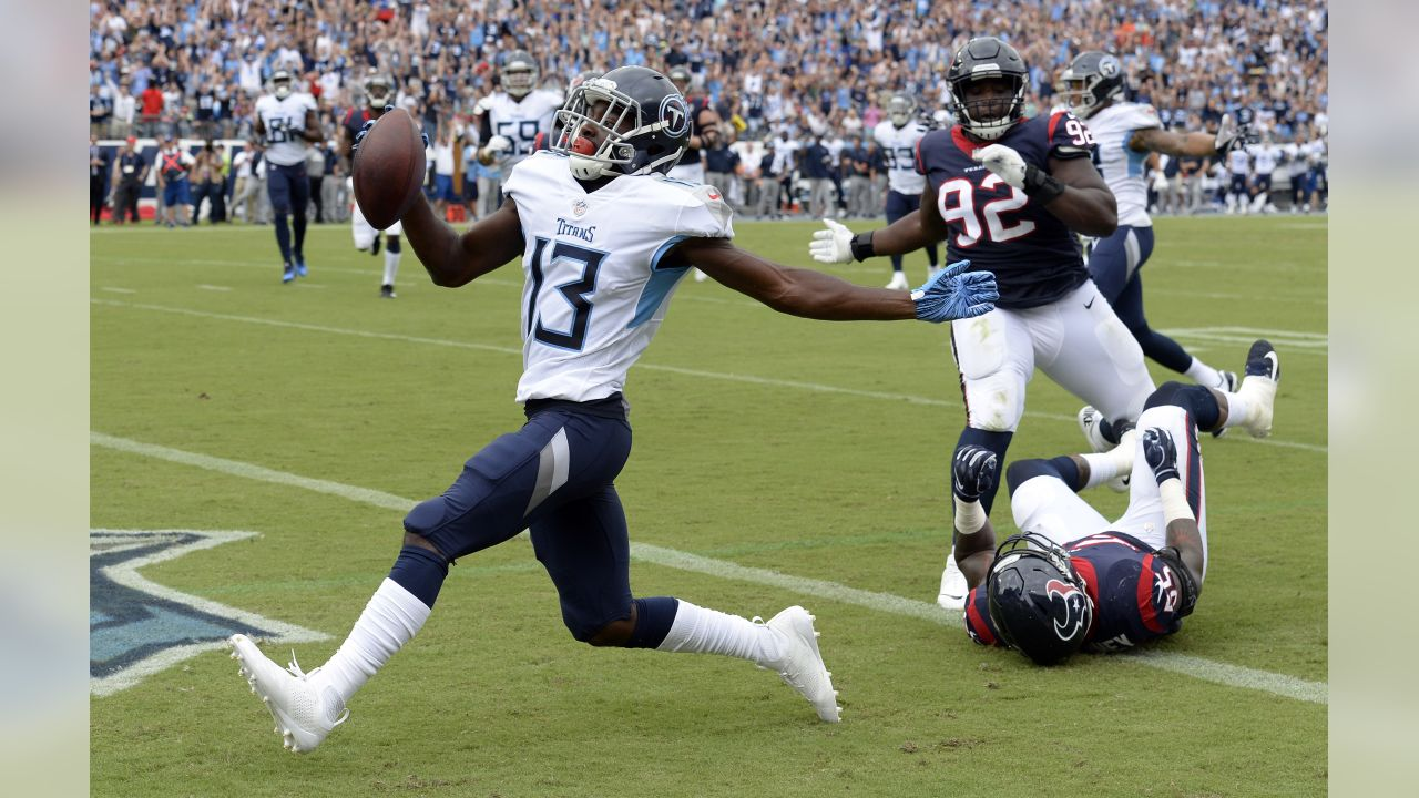 Tennessee Titans wide receiver Taywan Taylor (13) scores a touchdown ahead of Houston Texans defensive tackle Brandon Dunn (92) in the first half of an NFL football game Sunday, Sept. 16, 2018, in Nashville, Tenn.(AP Photo/Mark Zaleski)