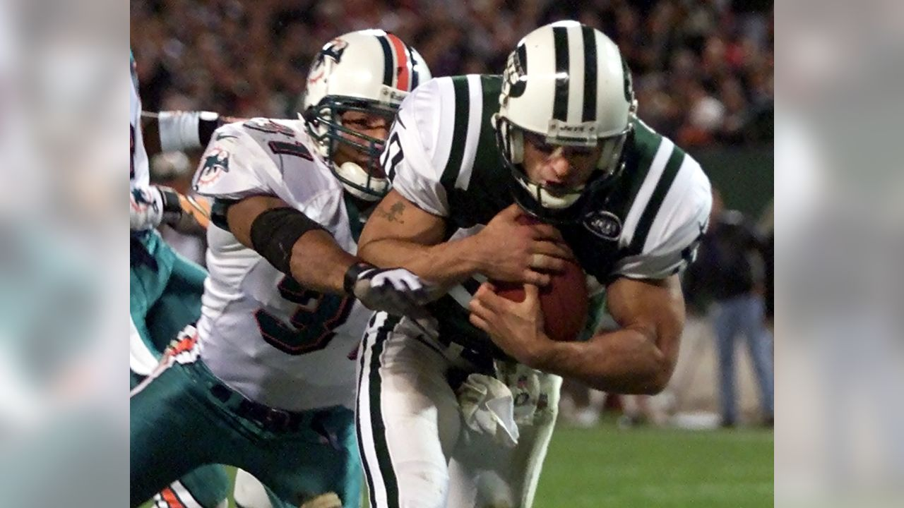New York Jets wide receiver Wayne Chrebet, right, scores a touchdown as Miami Dolphins safety Brock Marion (31) defends during the second quarter Monday, Oct. 23, 2000, in East Rutherford, N.J. (AP Photo/John T. Greilick)