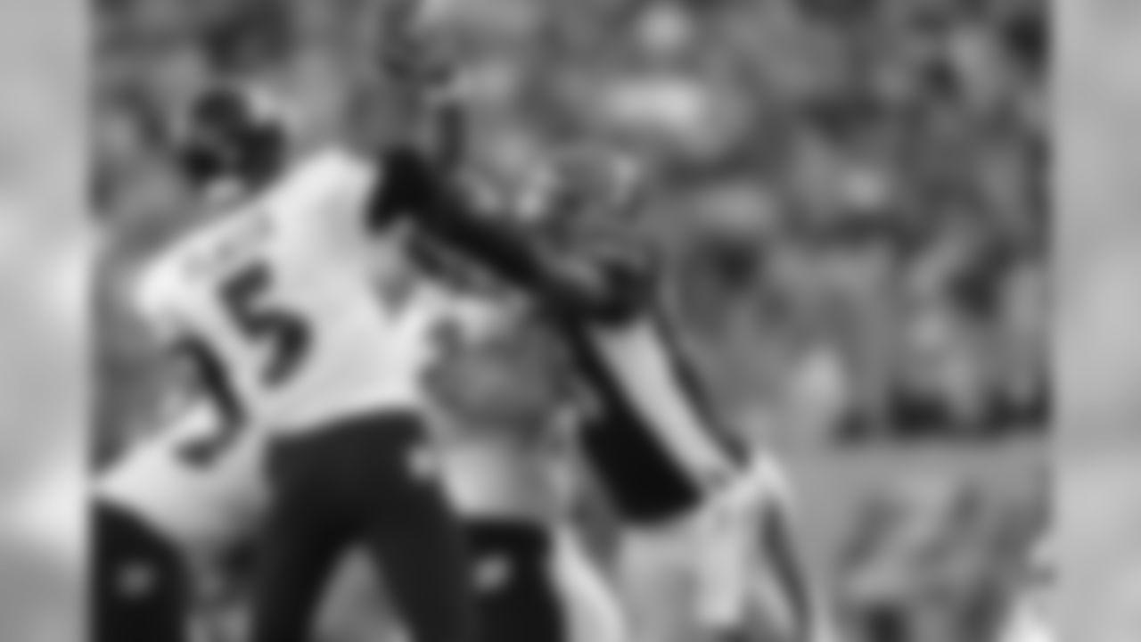 Carlos Dunlap hits Joe Flacco as he throws during a 2014 contest against Baltimore.