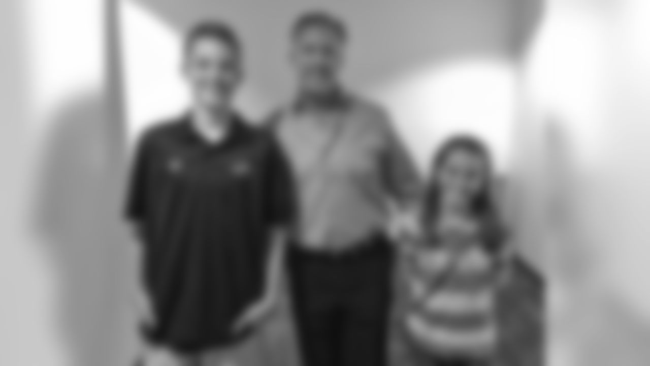 Broncos EVP/GM John Elway pauses for a picture with Jay and Lyndsey Olson, the children of 9NEWS (KUSA) photographer Brian Olson.