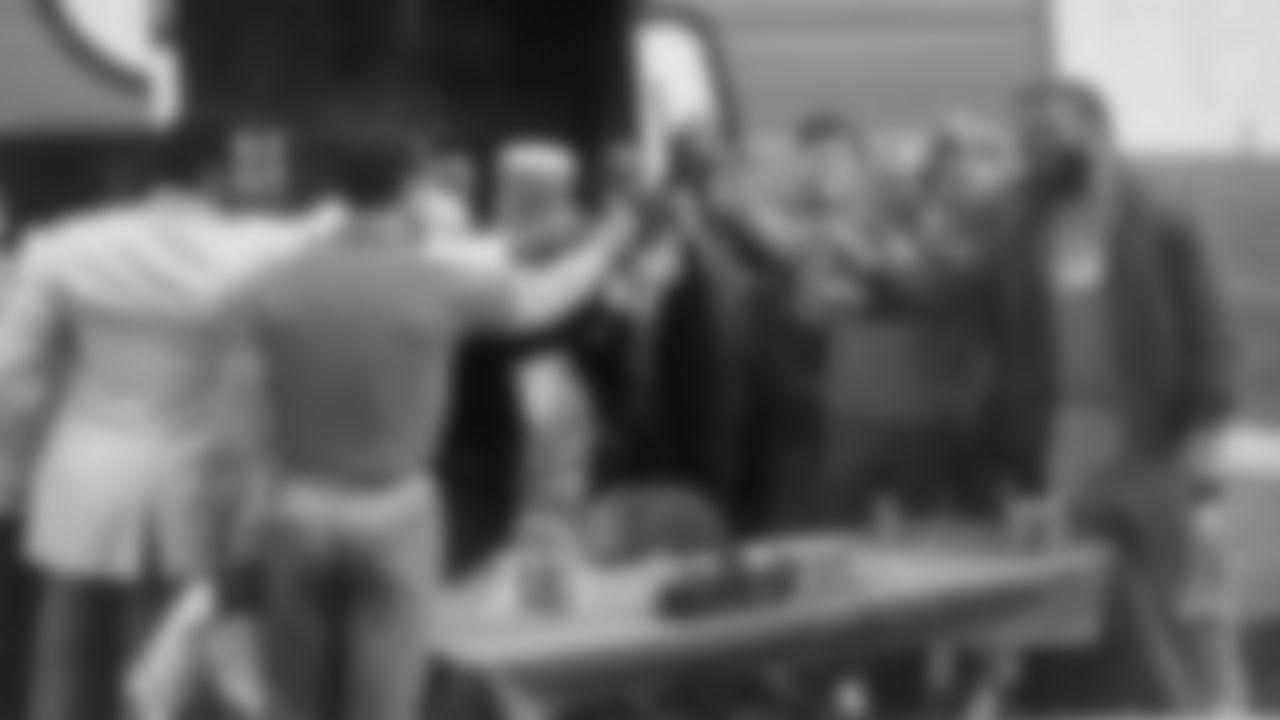Linebacker Tom Jackson, defensive back Steve Foley, owner Pat Bowlen, quarterback John Elway and other members of the Broncos make a toast with Orange Crush soda.