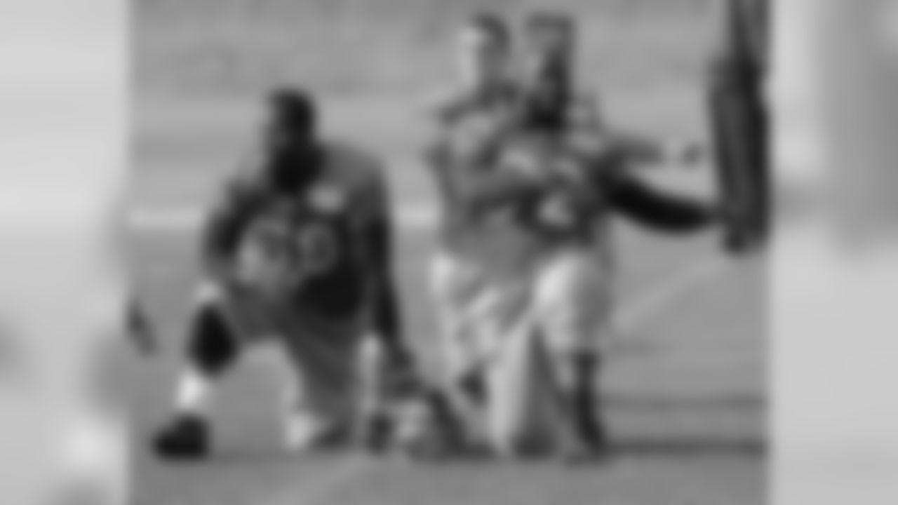 DE Elvis Dumervil and LB Von Miller stretch before practice.