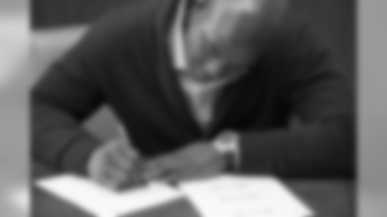 DeMarcus Ware signs his NFL free agency contract on March 12, 2014.