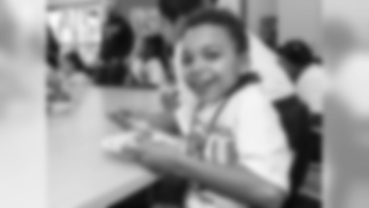 Picture of a happy boy at a table eating cake in a room full of classmates and adults.