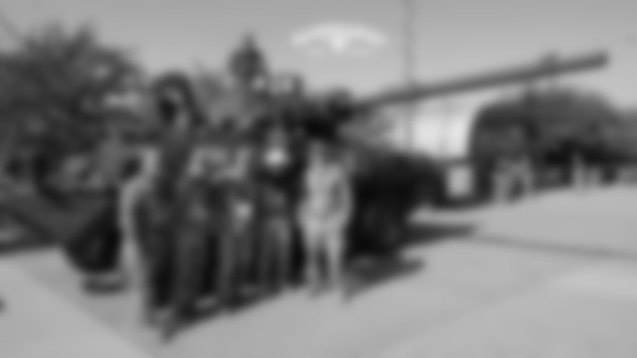 Big Red poses with members of the military in front of a tank