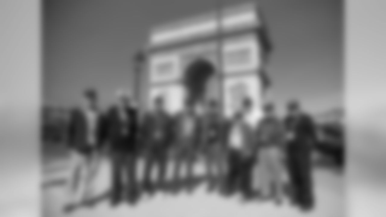 Veterans arrive in Paris and pose for a photo in front of the the Arc de Triomphe.