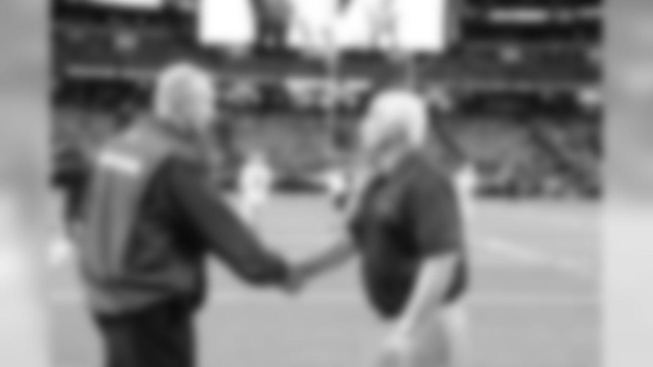 Mike Smith greets defensive coordinator Jim Haslett