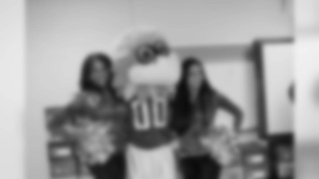 Atlanta Falcons Cheerleaders Denita C. and Rie O. smile with Freddie Falcon