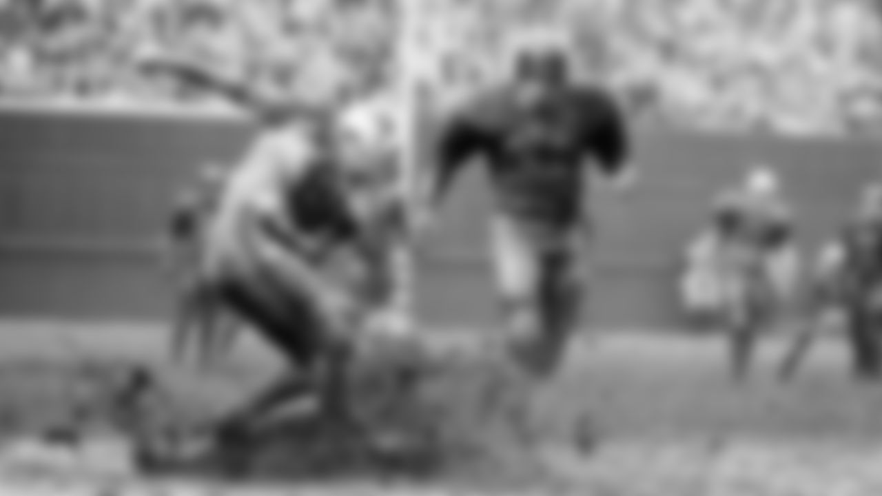 New York Giant Andy Nelson, almost obscured by sheet of flying mud and water, gets a face full of it as he hits the wet deck after knocking pass out of the hands of St. Louis Cardinals Jackie Smith (81) Nov. 15, 1964. Moving in on the action is Lou Slaby. Game was 10-10 tie. (AP Photo/Fred Waters)
